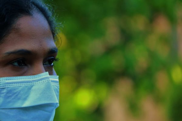 Farbige Frau trägt Mund-Nasen-Schutz