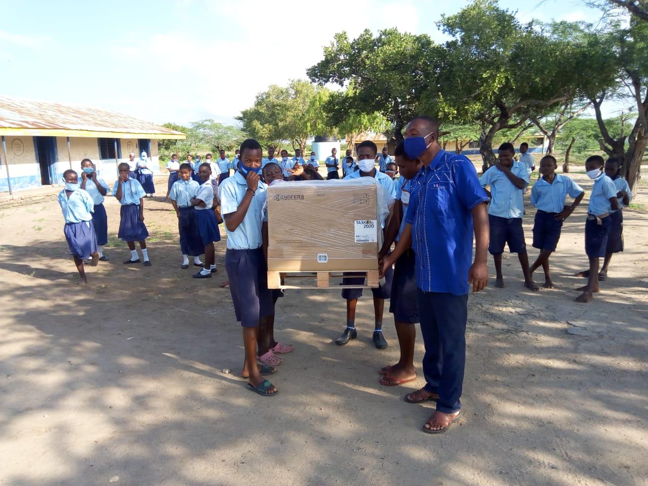 Ein Kopiergerät wird der Primary School in Maziwa überreicht.